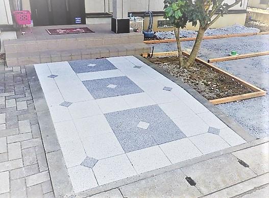 石材をデザインしたおしゃれなアプローチとアスファルトの駐車場